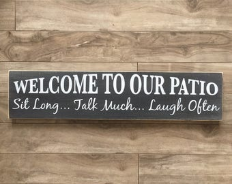 Welcome to our patio, sit long, talk much, laugh often sign - Outdoor sign on pine