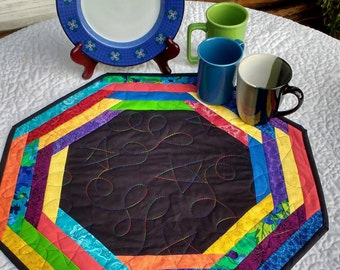 Quilted Table Topper. Black Center surrounded by Bright Colors. Centerpiece Mat. Octagonal. Reversible. Approx. 20 inches across.