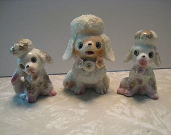 Family of 3 poodle figurines. White poodles with spaghetti trim, gold leaf, flowered collars. Adorable mid century collectibles.