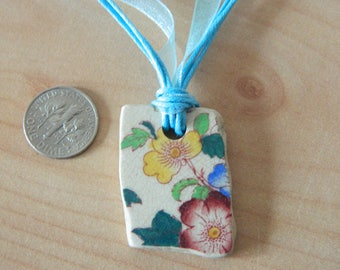 Beautiful sea pottery pendant with flower details on a blue organza necklace