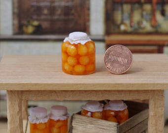 A large jar of mandarin.Canned in miniature banks. Miniature pickled fruit jars for a dollhouse. Miniature Mandarins. On a scale from 1/12.