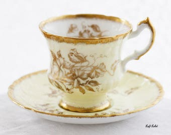Paragon Bone China, by appt. to Her Majesty the Queen, England,  teacup, a pale yellow base, a floral goldgilt design, thick goldgilt rims
