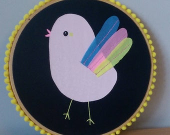 Little bird wall hanging adorned with pom pom trimming