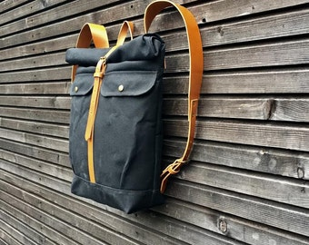 Black waxed canvas backpack with roll to close top and vegetable tanned leather shoulder straps