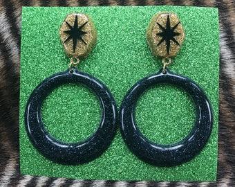 Black and gold atomic star dangle glitter resin earrings