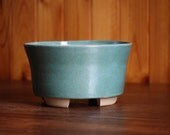 Round planter pot in a glossy speckled duck egg blue glaze
