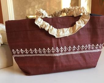 Dark brown bag with handpainted warli design & beige handle.
