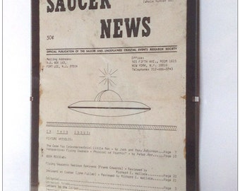 Aged reproduction of Saucer News magazine from 1966 in clip frame.