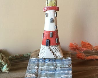 Rustic clay lighthouse mounted on driftwood, red, white, yellow, blue and white
