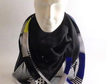 Foulard en voile de laine noir orné d'une bordure réalisée d'un patchwork de conton imprimé graphique N/B, coton fluo, soie bleu et lurex.