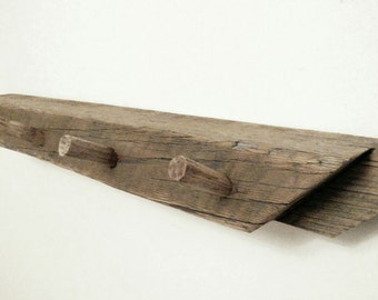 rustic coat hanger made from antique knee brace and hand hewn barn pegs