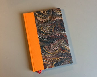 Hand bound A5 notebook journal quarter bound with orange book cloth and marble paper bookbinding