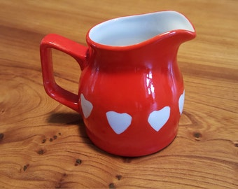 Red cream jug with white hearts