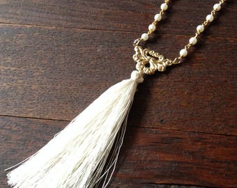 Ivory white silk tassel necklace with pearl rosary beads and a classic rosary centerpiece.