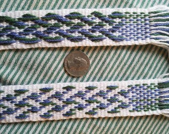 White hand-woven inkle belt with blue and green Celtic knot-work pattern.