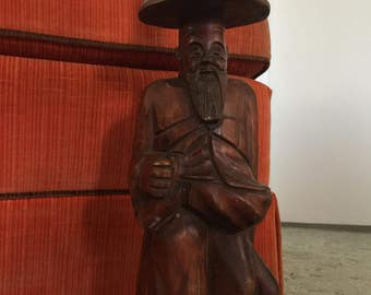Wooden statue of happy Chinese man