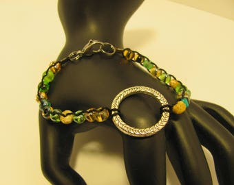 Green and brown glass bead bracelet with silver ring centerpiece