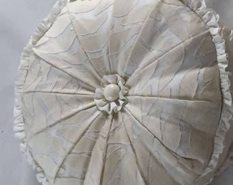 cream round cushion with frill, buttons in centre