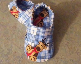 Slippers size 7 flannel reindeer theme. Blue check background. Item lined. Slip resist bottom. Gathered sole. 6 inch finished bottom.