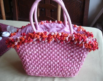 SALE:  25.00  A Pink Rattan Basketweave Purse,Pink wrapped handles. Handbag Opening Trimm  ed in Red, Orange Tan Wooden Beads