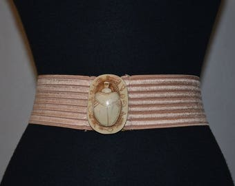 80s elastic cinch stretch belt. Nude flesh pink with egyptian scarab dimensional buckle. hierogylphics. ribbed elastic deadstock. M Beatle