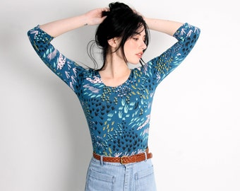 Thistle Long Sleeved Crop Top in Pale Pink, Yellow Ochre, Mint Green and Black on Bay Blue