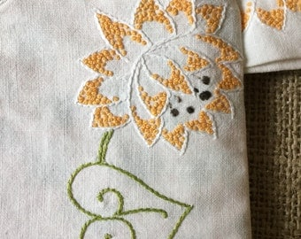 "6"" x 6"" Embroidered pouch with orange and green flowered lining."