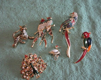 Animal brooches, mostly birds, one tiger