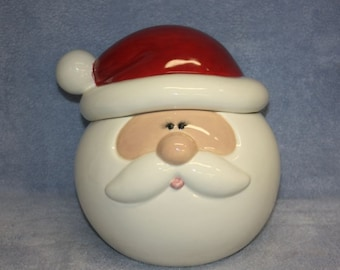 Handpainted ceramic Santa Cookie Jar with a big round face and red Santa Hat