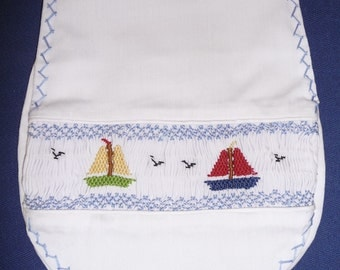 Hand smocked bib with sailboats.