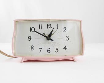 A Pink Bedside Clock -  'General Electric' Clock - Model 7267K - Electric Clock With Alarm - Curved Pink Body  - Curved Clear Plastic Face