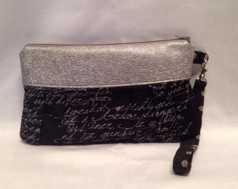 Wristlet/Clutch purse in a classy text print with pleated front, zipper closure and detatchable hand strap