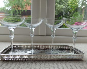 Four tall-stemmed large-bowled champagne glasses