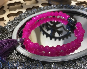 Hot Pink glass beaded flexible bracelet with a Pewter Buddha Head and bright Purple Tassel.