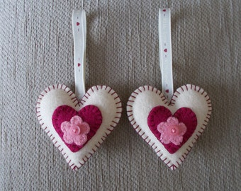 A handcrafted  pair of cream and rose pink felt heart hanging decorations