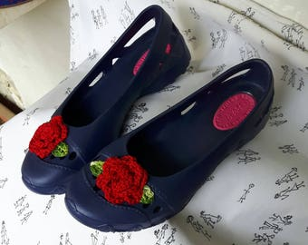 Blue plastic shoes with red handmade knitted flowers