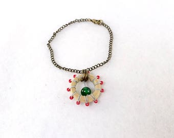 Wooden bracelet with green and red little pearls
