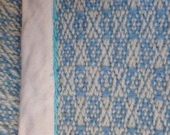 Babydeken, handgeweven wol. Lichtblauw en wit. Veilig voor kinderen. ±116 x 80 cm.