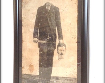 Aged reproduction framed Victorian print of a headless gentleman.