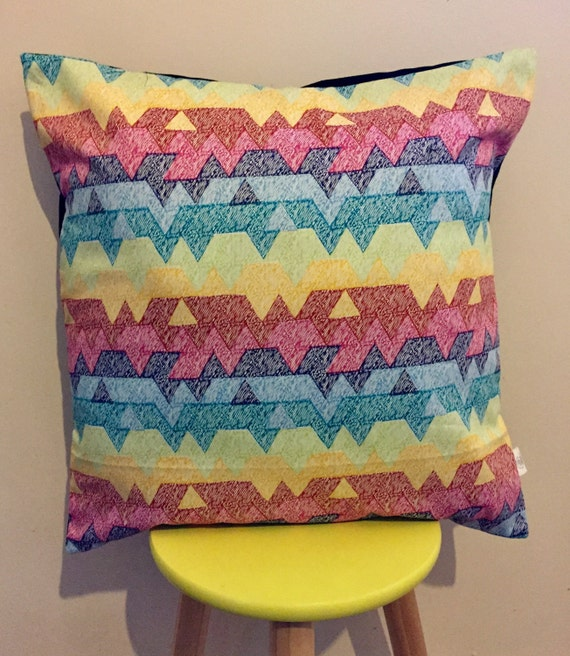 Multicoloured geometric printed cushion cover. Yellow, green, red, pink, blue, teal,