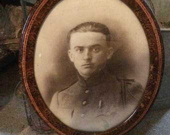 Oval frame with a French young soldier's portait during the First World War. 1910s. Burr elm imitation.