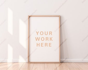 Vertical Poster with Wooden Frame Mockup standing on the floor in light interior / Blank canvas