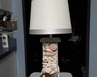 Grey seashell decorated wooden lamp and shade.