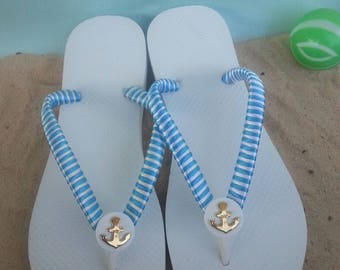 White flip flops with blue and white satin ribbon and gold anchor button.  Beach white and blue flip flops with gold anchor button.