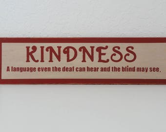 Painted wood sign: KINDNESS a language even the deaf can hear and the blind may see.