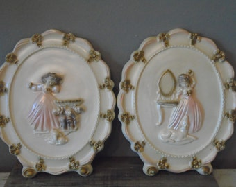 Set of 2 3D vintage plaster / chalkware oval girl's wall art with girl in pastel pink and gold at vanity table and birdbath