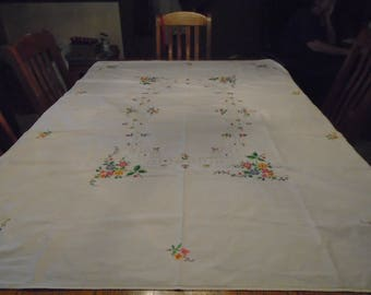 Large white cotton tablecloth with hand embroidered cross stitched colorful flowers along border and center 46 x 65