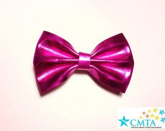 One hot pink faux leather hair bow. Portion of sale goes to charity. Cruelty-free.