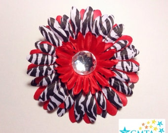 One red and zebra hair flower with rhinestone. Portion of sale goes to charity.