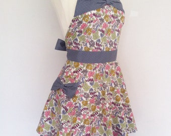 Retro apron with bow, earth coloured leaves on a white fabric.